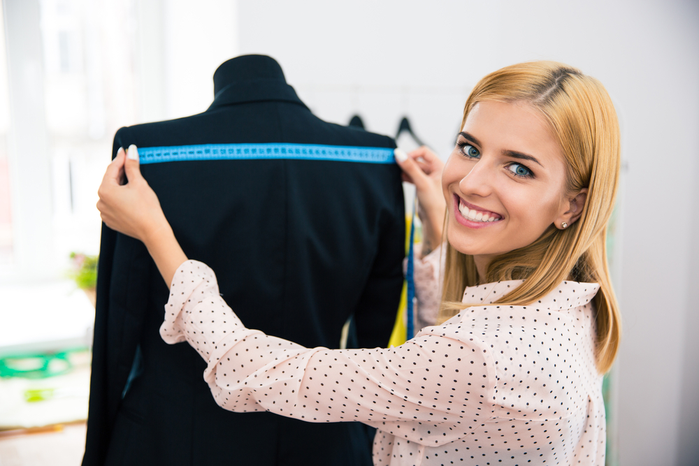 Smiling female tailor measuring tape jacket on mannequin and looking at camera