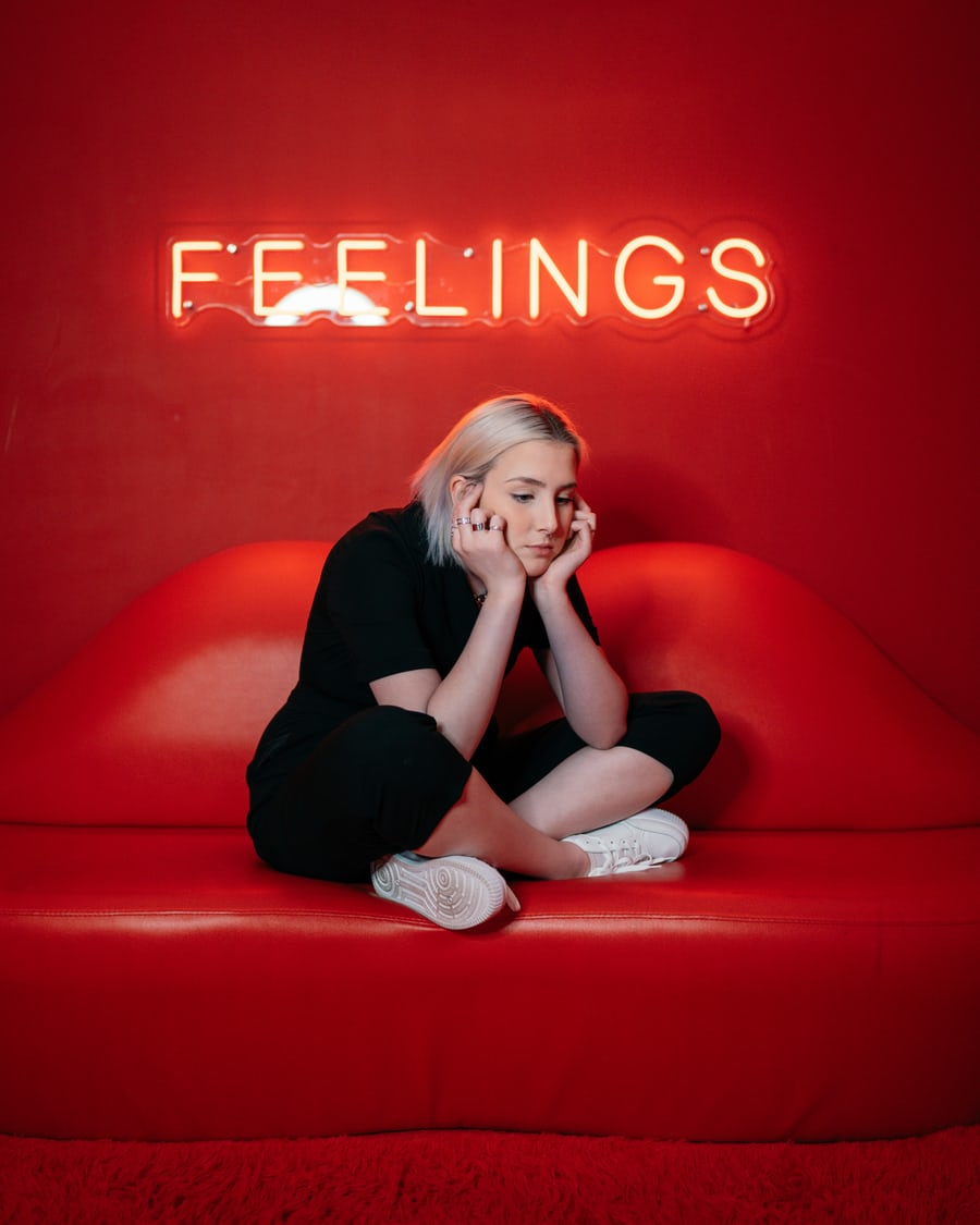 girl sitting in a red room thinking about feelings