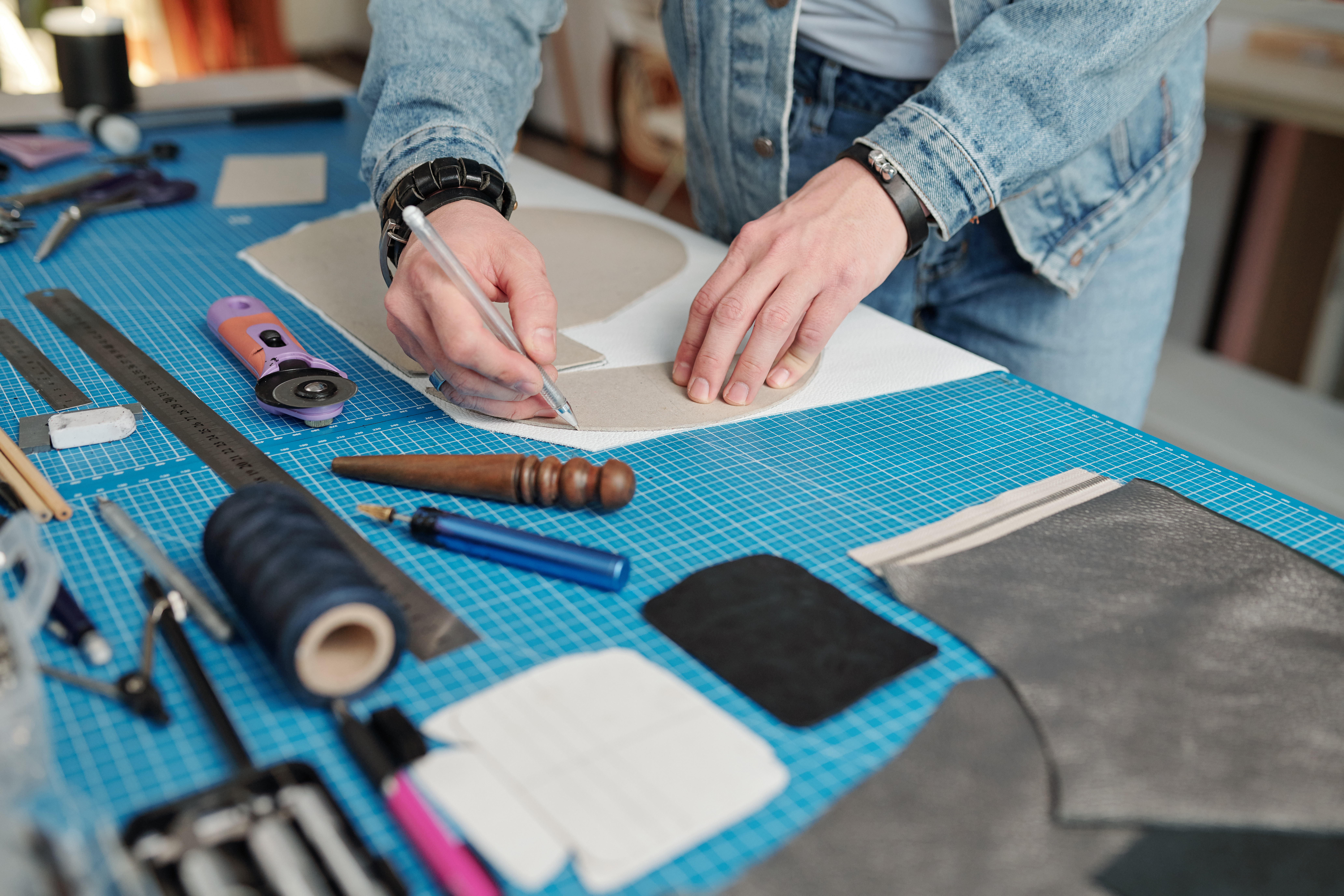 young-leatherworker-in-workwear-outlining-paper-pa-5H33WJL